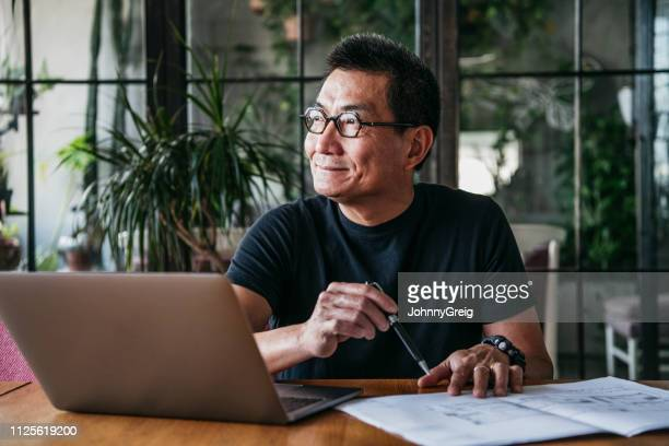 mature chinese man using laptop at home - satisfaction stock pictures, royalty-free photos & images