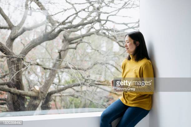 mature chinese woman relaxing at home with mug of tea - mid length hair stock pictures, royalty-free photos & images