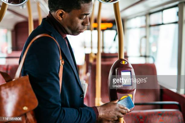 mature commuter in london using contactless payment for the fare - paying stock pictures, royalty-free photos & images