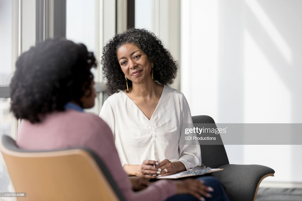 Mature counselor listens compassionately to unrecognizable female client : Stock Photo