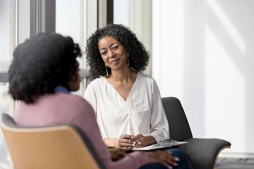 Mature counselor listens compassionately to unrecognizable female client 1207514066