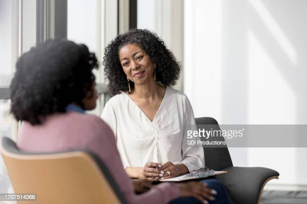 mature counselor listens compassionately to unrecognizable female client - listening stock pictures, royalty-free photos & images