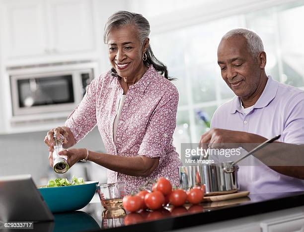 A mature couple, a man and woman in their kitchen preparing a meal.