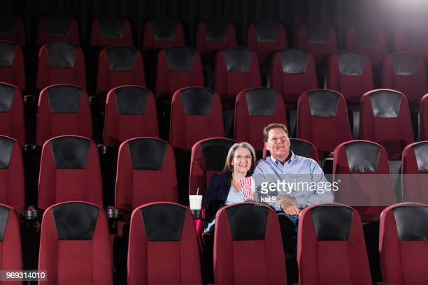 mature couple alone in movie theater - film screening stock pictures, royalty-free photos & images