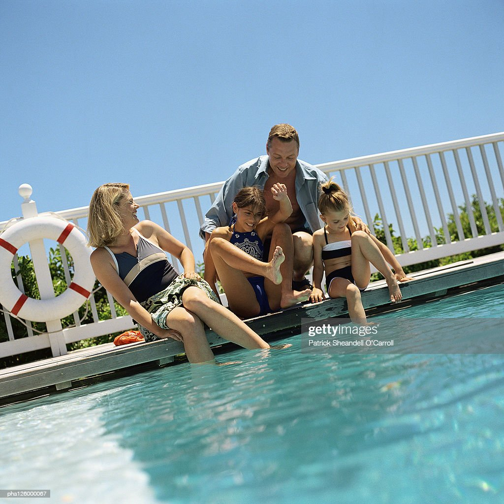 Mature couple and children on side of swimming pool : Stockfoto
