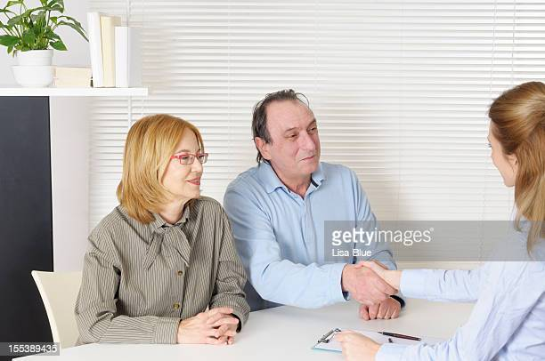 Mature Couple and Counselor Handshaking