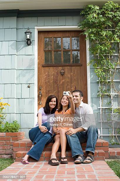 Mature couple and girl (11-13) photographing selves outside house door