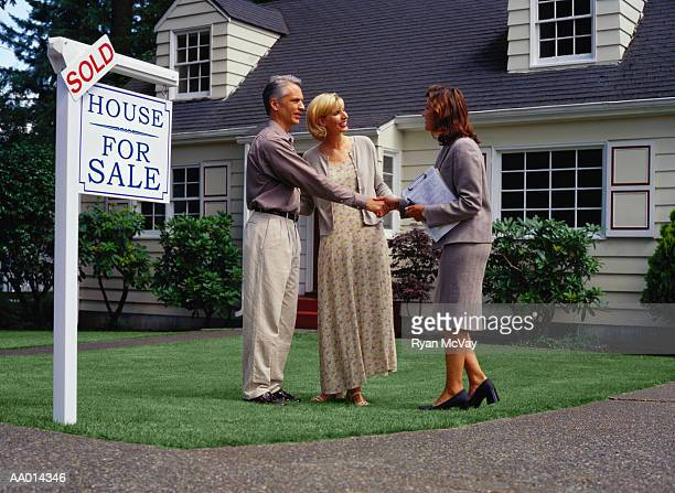 Mature couple and real estate agent standing in front of sold house