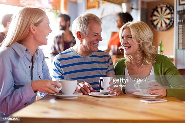 Couple d'âge mur et leur fille assise dans un café