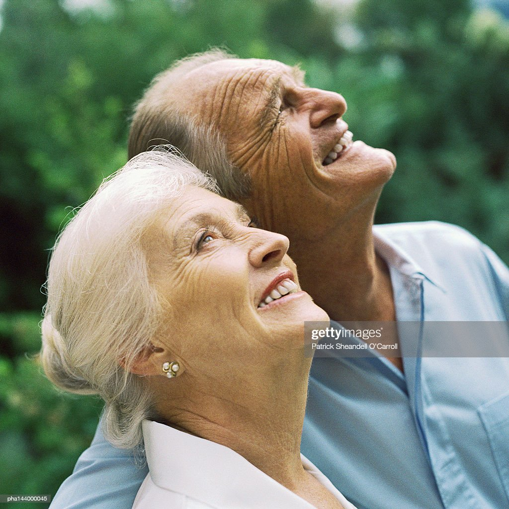Mature couple arm in arm, looking up : Stockfoto