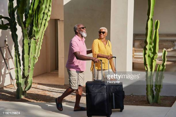 a mature couple arrive at a holiday villa - paradise stock pictures, royalty-free photos & images