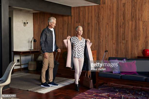 mature couple arriving to rental flat, with suitcases and bag - absence stock pictures, royalty-free photos & images