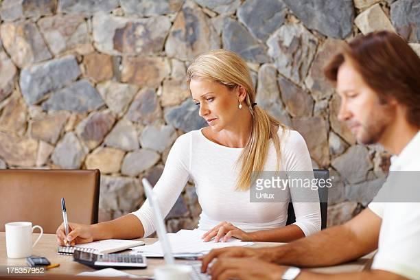 Casal na Mesa de Jantar trabalhar no computador portátil em casa e finanças