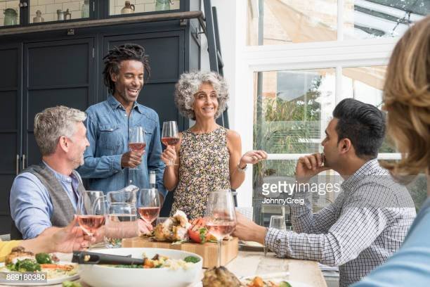 Mature couple at dinner table with wine glasses talking to friends