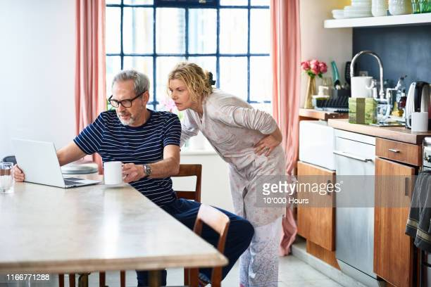 mature couple at home using laptop to plan home finances - routine stock pictures, royalty-free photos & images
