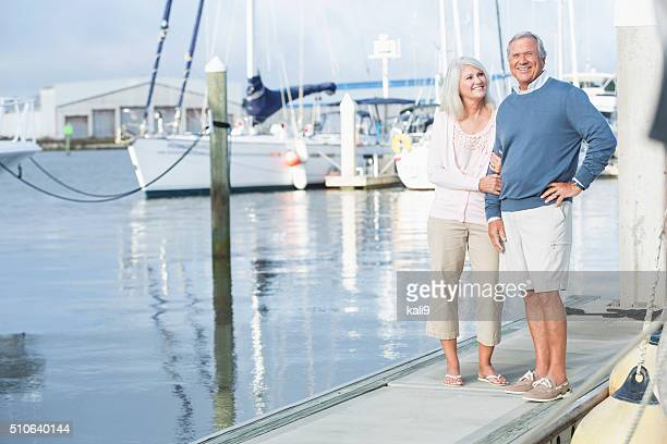 Mature couple at marina standing on dock