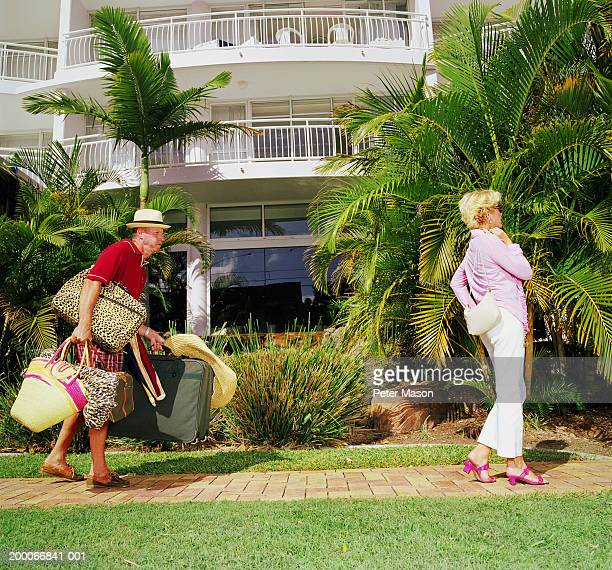 Mature couple at resort, man struggling with suitcases