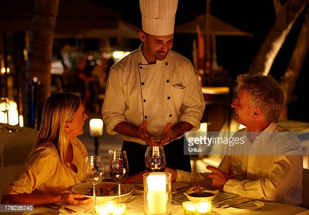 mature couple at restaurant ordering food and drinks from the waiter - dining stock photos and pictures