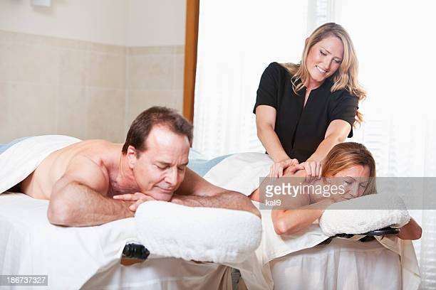 Mature couple at spa with massage therapist