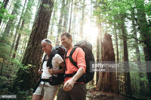mature couple backpacking in forest - estilo de vida ativo imagens e fotografias de stock