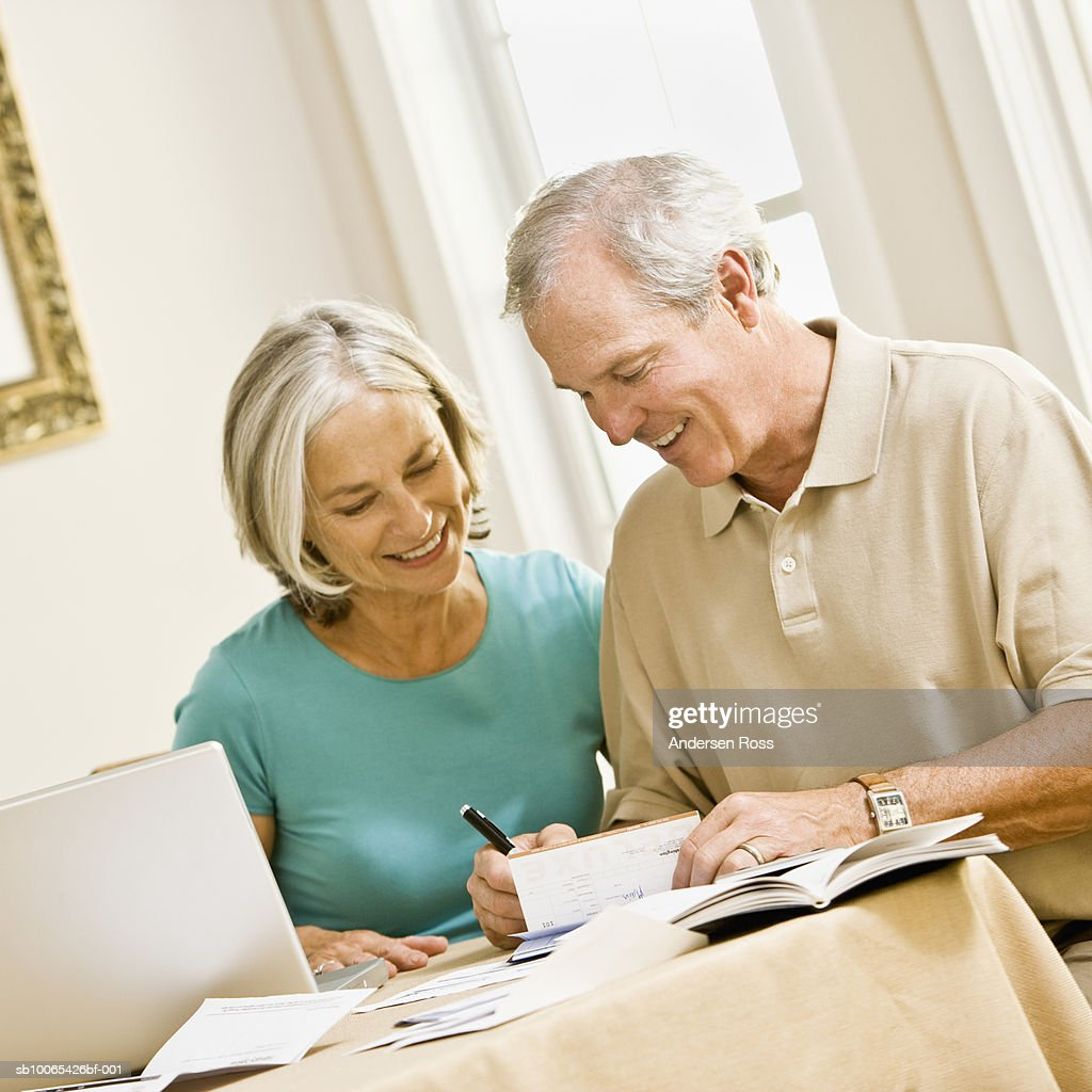 Mature couple balancing check book in front of laptop : Foto stock