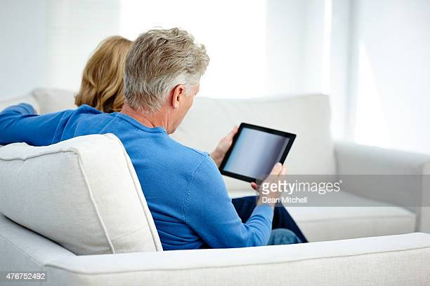 Mature couple browsing the internet on a digital tablet
