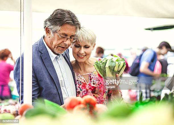 Mature couple buying food on the street market