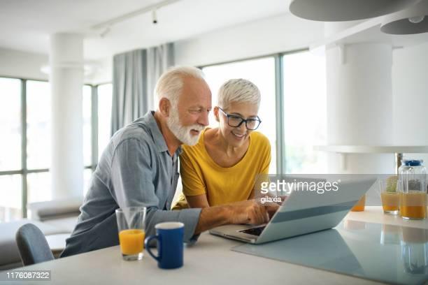 mature couple buying some goods online - coppia anziana foto e immagini stock