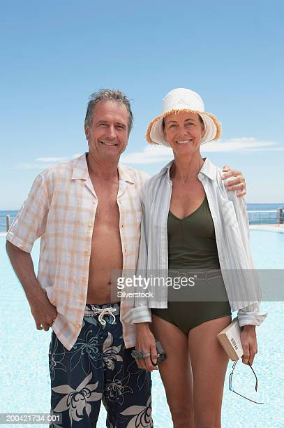 Mature couple by pool, man with arm around woman, smiling, portrait
