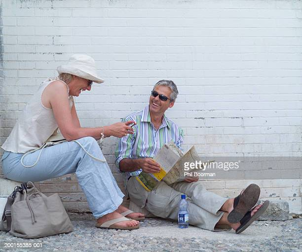 Mature couple by wall, man holding map, woman using mobile phone