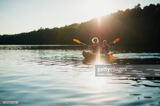 mature couple canoeing at a lake. - active lifestyle stock pictures, royalty-free photos & images