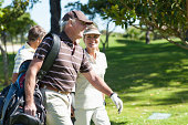 Mature couple carrying golf bags