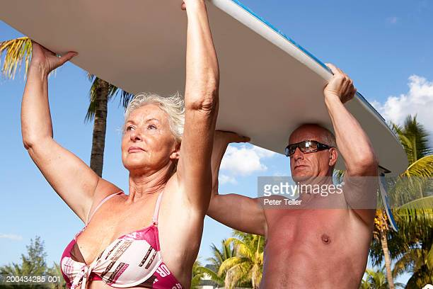 Mature couple carrying surfboard, close up, low angle