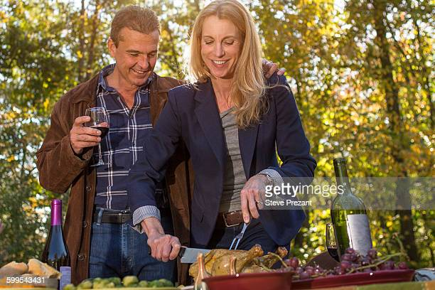 Mature couple carving roast chicken at garden dinner party