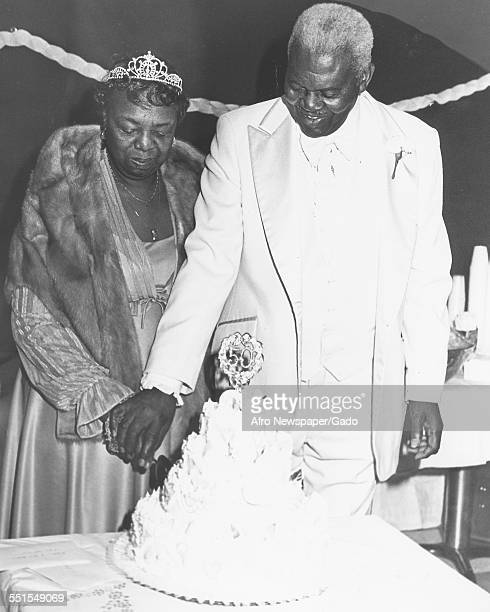 A mature couple celebrating their 50th wedding anniversary wearing their party clothes and standing by a large tiered celebration cake November 6 1981
