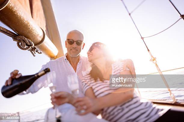Mature couple celebrating with champagne on a sunset yacht cruis