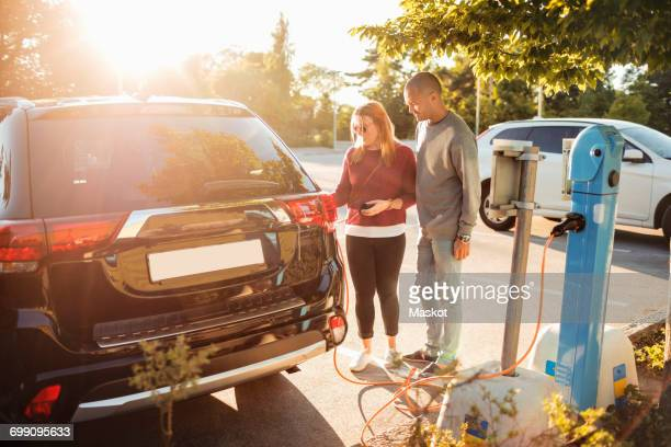 Mature couple charging electric car at station on sunny day