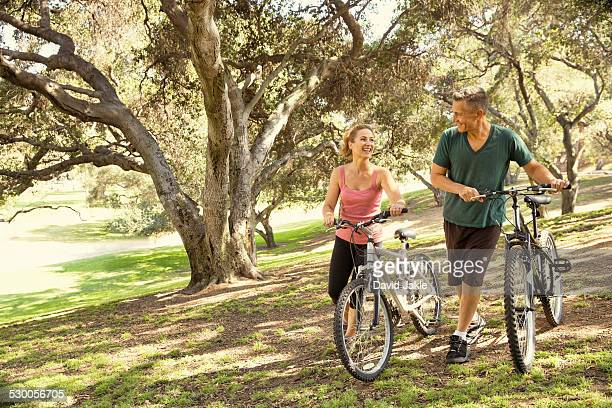 Mature couple chatting and pushing bicycles through park
