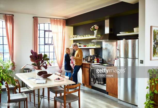 mature couple chatting in kitchen and doing the dishes - couples showering stock pictures, royalty-free photos & images