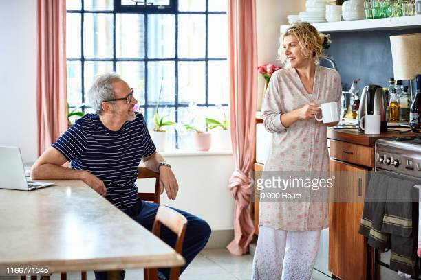 mature couple chatting in kitchen over morning coffee - mature couple stock pictures, royalty-free photos & images