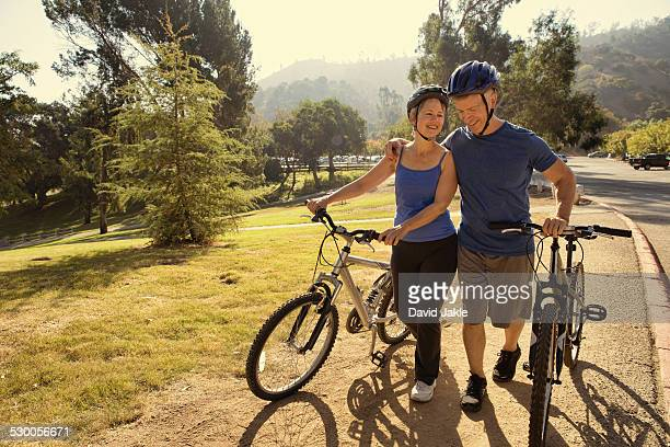 Mature couple chatting whilst pushing bicycles in park