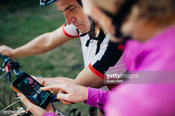 mature couple checking tracking app after biking trip. - eskapismus stock-fotos und bilder