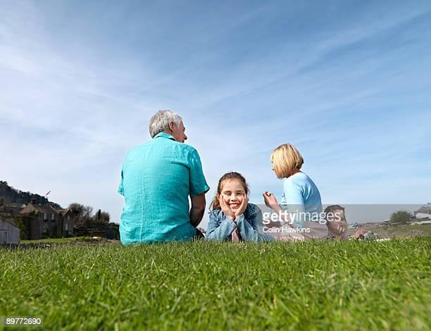 mature couple & children relax on grass - ポーロック ストックフォトと画像