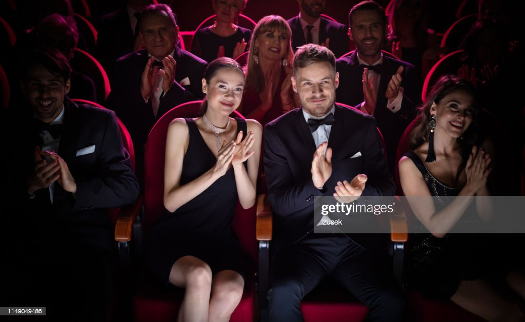 Mature couple clapping while watching opera : Stock Photo