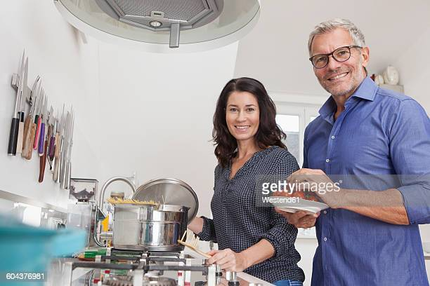 Mature couple cooking in kitchen