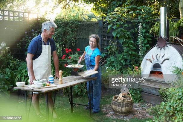 mature couple cooking pizzas in their garden - pizza oven stock photos and pictures