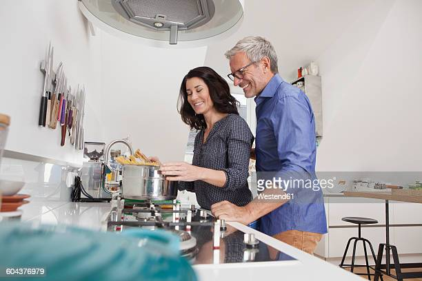 Mature couple cooking spaghetti in kitchen