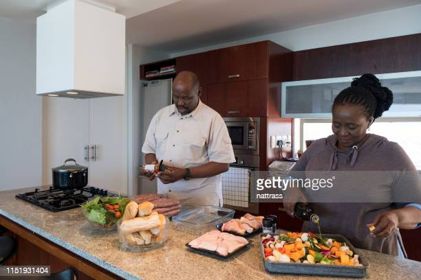 mature couple cooking together in kitchen - fat nutrient stock pictures, royalty-free photos & images
