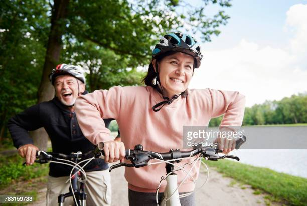 mature couple cycling beside lake, laughing - cycling helmet stock photos and pictures