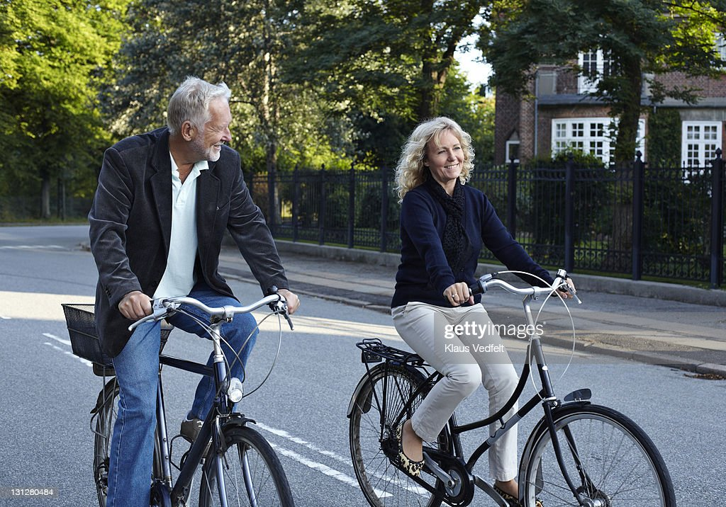 Mature couple cycling in residential neighborhood : Stock Photo